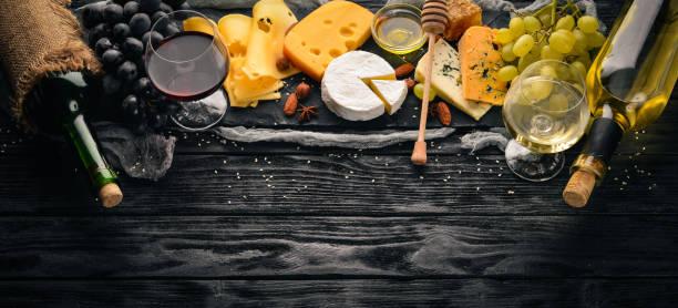 Uma grande variedade de queijos, queijo brie, gorgonzola, queijo azul, uvas, vinho de mel, nozes, vermelho e branco, em uma mesa de madeira. Vista superior. Espaço livre para texto. - foto de acervo