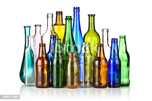 Back lit photo of a large assortment of multi colored glass bottles shot on reflective white backdrop. The bottles are arranged so that the taller are in the center at the background while the smaller are at the sides and in the foreground. The bottles are of different shapes, color and sizes. Visible reflection of the bottles in the foreground. High key DSLR studio photo taken with a Canon 5D Mk II.