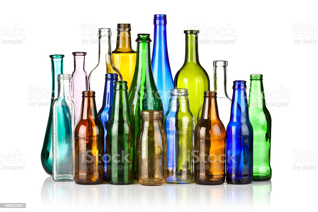 Large assortment of multicolored glass bottles on reflective white backdrop stock photo
