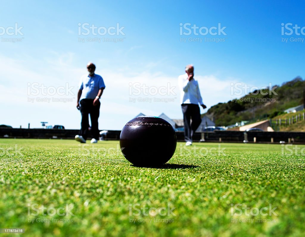 A large ball in the grass with two men in the distance stock photo