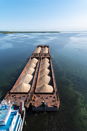 A large barge with sand sails along the coast along the wide Volga river