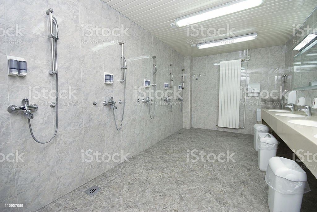 Large bathroom with a number of showers and sinks royalty-free stock photo
