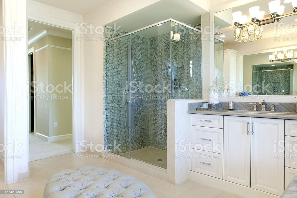 Large bathroom with white cabinets and green tiles stock photo