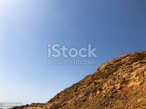 A large beautiful majestic stone sandy mountain, a mound in the desert against a blue sky. Landscape.