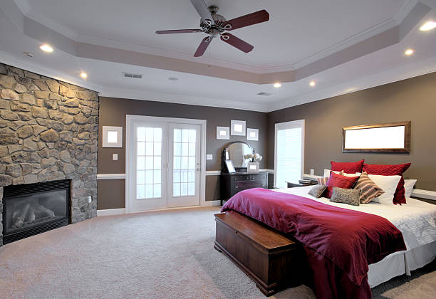Large Bedroom Interior Interior of a large modern bedroom with a fireplace and ceiling fan. Horizontal format. ceiling fan stock pictures, royalty-free photos & images