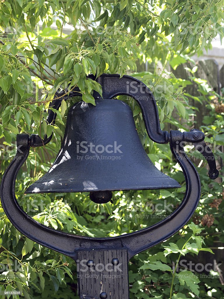 Large black bell mounted on pole in garden royalty-free stock photo