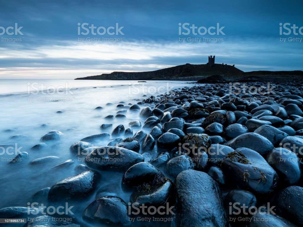 Large black egg shapred rocks at Embleton Bay with Dunstanburgh castle in the background. stock photo