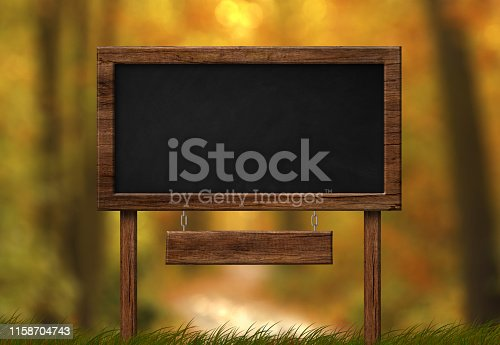 istock Large blackboard with wood frame and autumn forest background 1158704743