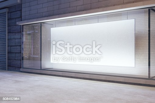 istock Large blank banner in a shop window at night 508452984