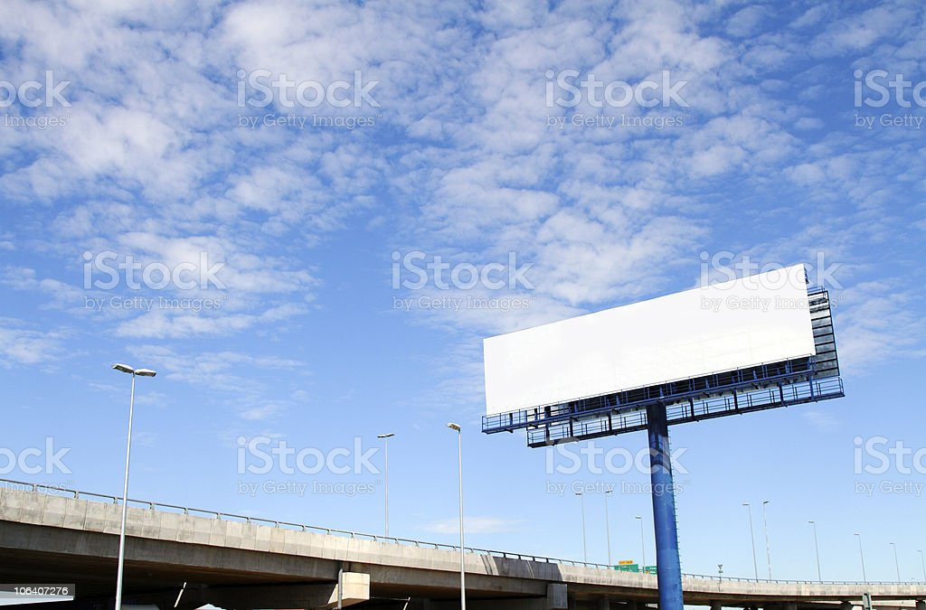 A large blank billboard near a main road on a cloudy day stock photo