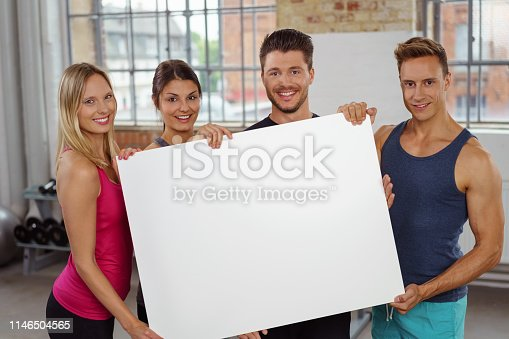 istock Large blank white poster in hands of fit adults 1146504565