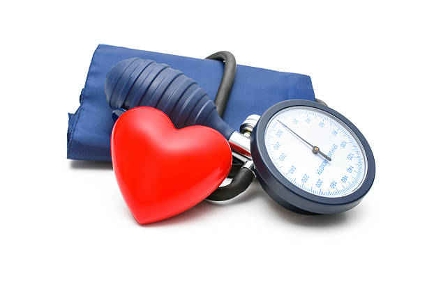 Large blood pressure gauge with a red heart leaning on it Blood Pressure gauge and heart isolated on white background hypertensive stock pictures, royalty-free photos & images