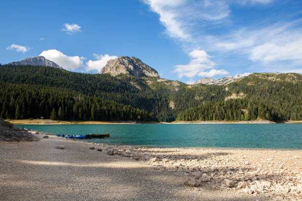 large blue lake in the mountains - lakeshore stock photos and pictures