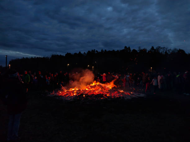 Large bonfire surrounded by people next to a forest stock photo