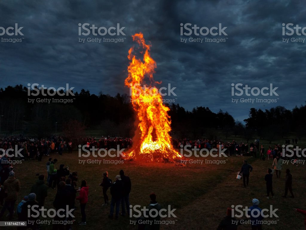 A large bonfire which is many meters high is located in the middle of...