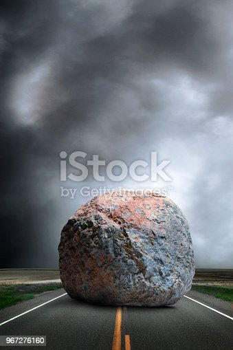A large boulder sits in the middle of a long straight rural road with ominous clouds on the horizon in the background.