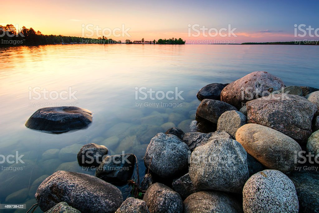 Large boulders on lake shore at sunset. Minnesota, USA stock photo