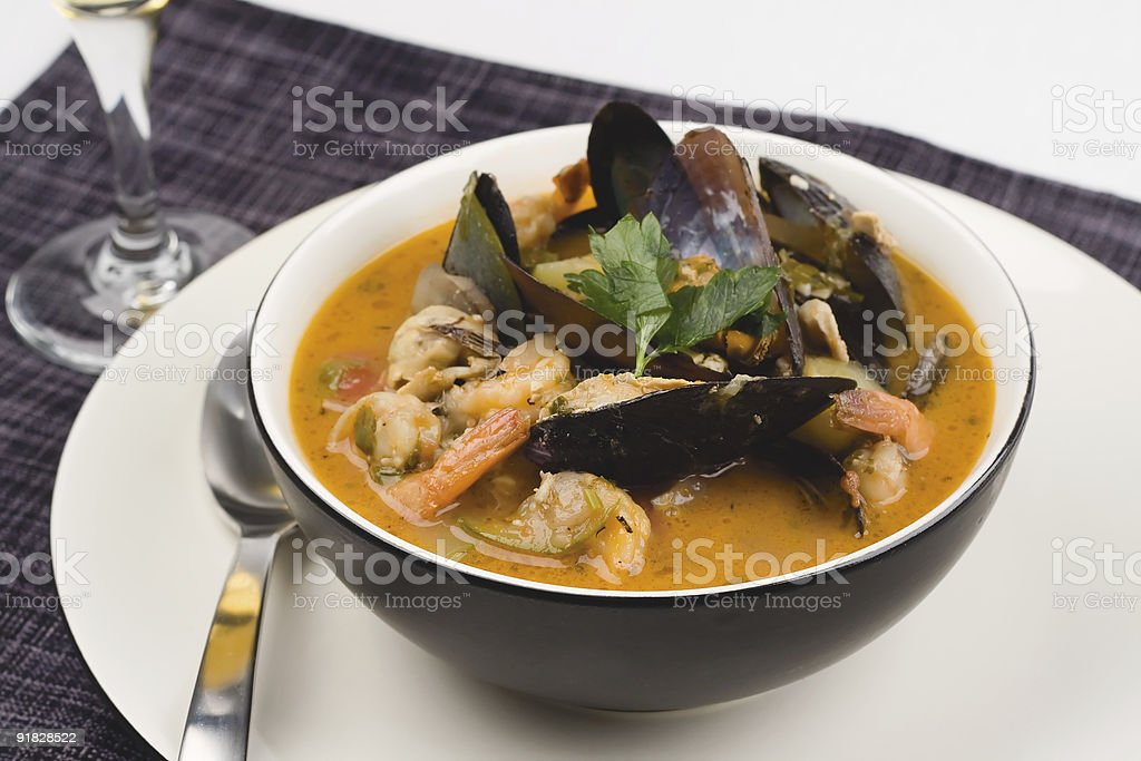 A large bowl of seafood soup on a white plate stock photo