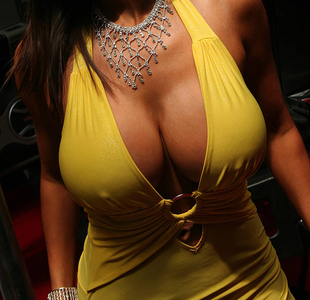 Large breasted woman in a yellow dress stock photo