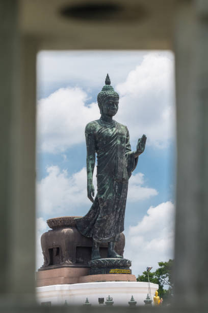 Large Bronze statue Walking Buddha with Frame Look through from Street Light Thailand Travel Concept. stock photo