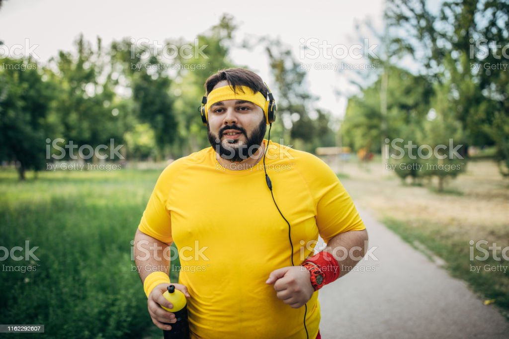One man, young overweight man jogging alone in park, listening music...