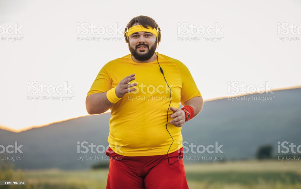 One man, young overweight man jogging alone one the street, listening...