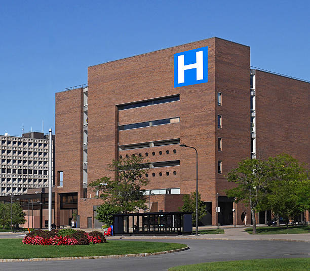 large building with h sign for hospital - hospital building stock photos and pictures