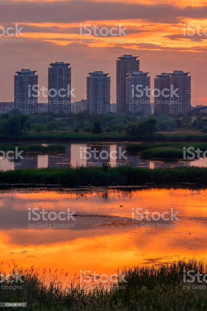 Large buildings skyscrapers in the sunset reflecting in the lake stock photo