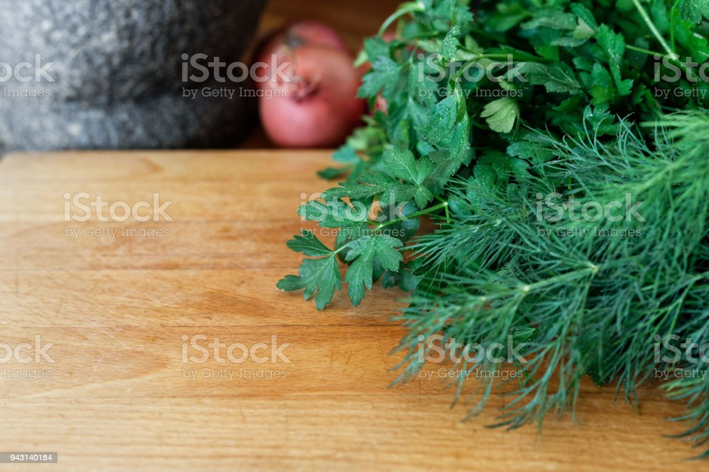 Large bunch of fresh herbs on wood chopping board. Space for text.