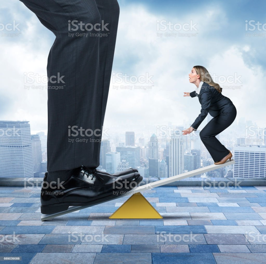 Large Businessman Holding Down One End Of Seesaw stock photo