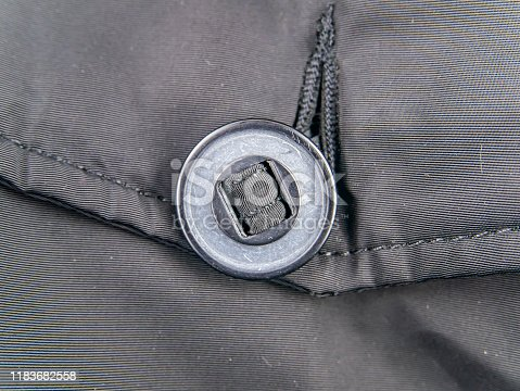 A large button on clothes. Clothing.