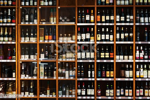 A large wooden cabinet filled with many different kinds of bottles of wine at a supermarket.