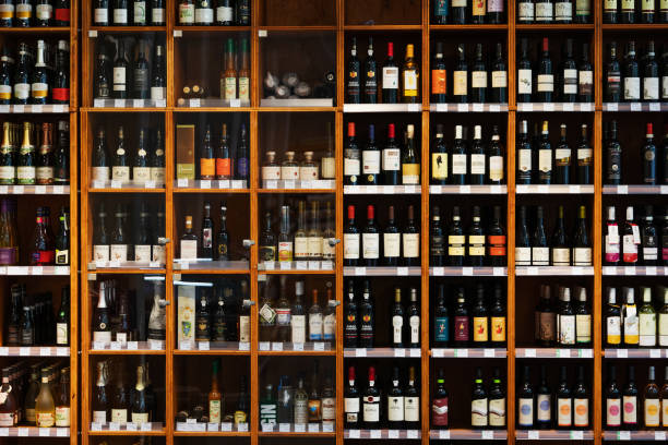 Large Cabinet With Many Bottles Of Wine At Supermarket A large wooden cabinet filled with many different kinds of bottles of wine at a supermarket. grocery aisle stock pictures, royalty-free photos & images