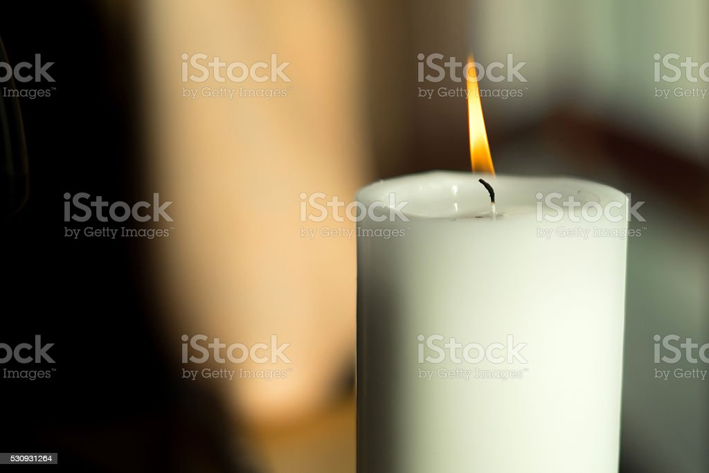 Large candle with a burning flame stock photo