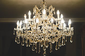 Beautiful old chandelier inside a room, illuminated.