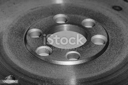 istock Large circle with lot of details close-up in grayscale. Vintage mechanism. Monochrome background of auto part with copy space. Retro device. 1002295002