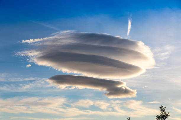 Large circular clouds (Altocumulus lenticularis duplicatus) in the sky Large circular cloud forms (Altocumulus lenticularis duplicatus V-39) in the evening sky over Malaga city, Spain. Airplane trace in the sky on the background altocumulus stock pictures, royalty-free photos & images