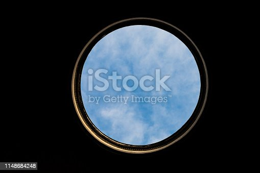 Large circular hole with golden frame and blue cloudy sky and black background. Seen from inside Phanteon building in Rome Italy. Free entrance to walk in the Phanteon.