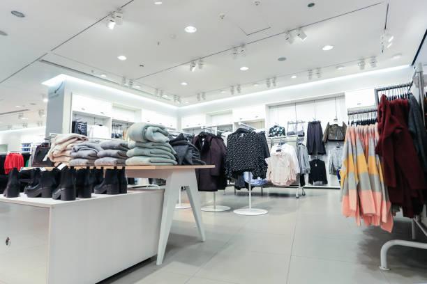 grote kleding supermarkt met verschillende kleding, broeken, schoenen, sjaals en handschoenen - kledingwinkel stockfoto's en -beelden