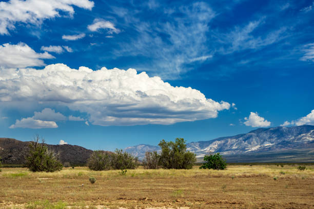 Large cloud over a valley with a view of the San Bernardino Mountains stock photo