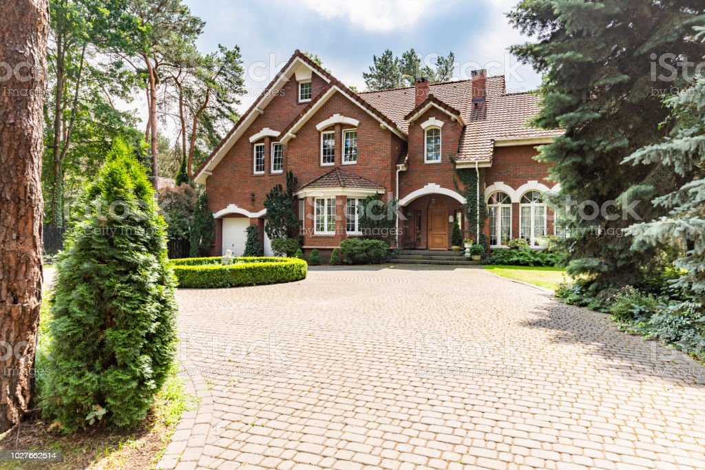 Large cobbled driveway in front of an impressive red brick English design mansion surrounded by old trees – zdjęcie