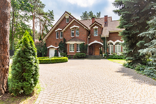 Large Cobbled Driveway In Front Of An Impressive Red Brick English Design Mansion Surrounded By Old Trees Stock Photo - Download Image Now