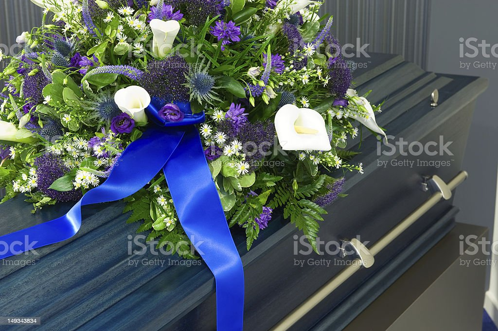 A large coffin in a morgue topped with flowers stock photo