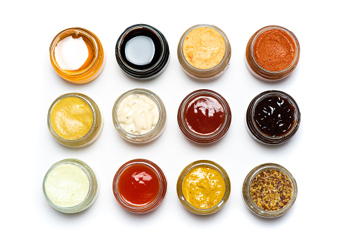 Large collection of sauces and spiced spreads in small jars isolated flat lay tabletop