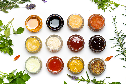 Large collection of sauces and spiced spreads in small jars isolated flat lay. Various herbs and dressings as mayo ketchup mustard soy sauce and many more