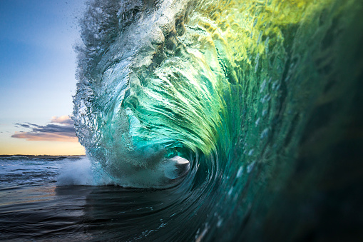 Large colourful wave breaking in ocean over reef and rock