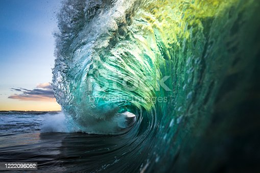 istock Large colourful wave breaking in ocean over reef and rock 1222096052