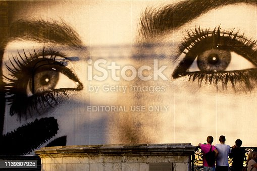 Boys staring at a large commercial billboard promoting cosmetics in Moscow at August 22nd, 2011.  Billboards are the oldest form of advertisements persuading an audience