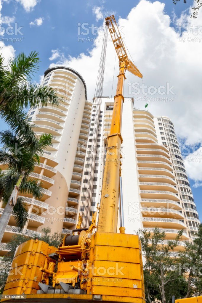 Large construction crane loading roof tile on top of highrise building under construction stock photo