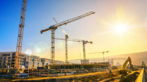 Large construction site including several cranes, with clear sky and the sun stock photo